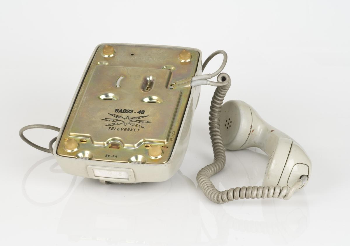 En gammel telefon med roterende tastatur. Telefonen er av plastog matell. Plasten er i gråfarge. Påført tekst på undersiden av telefonen.