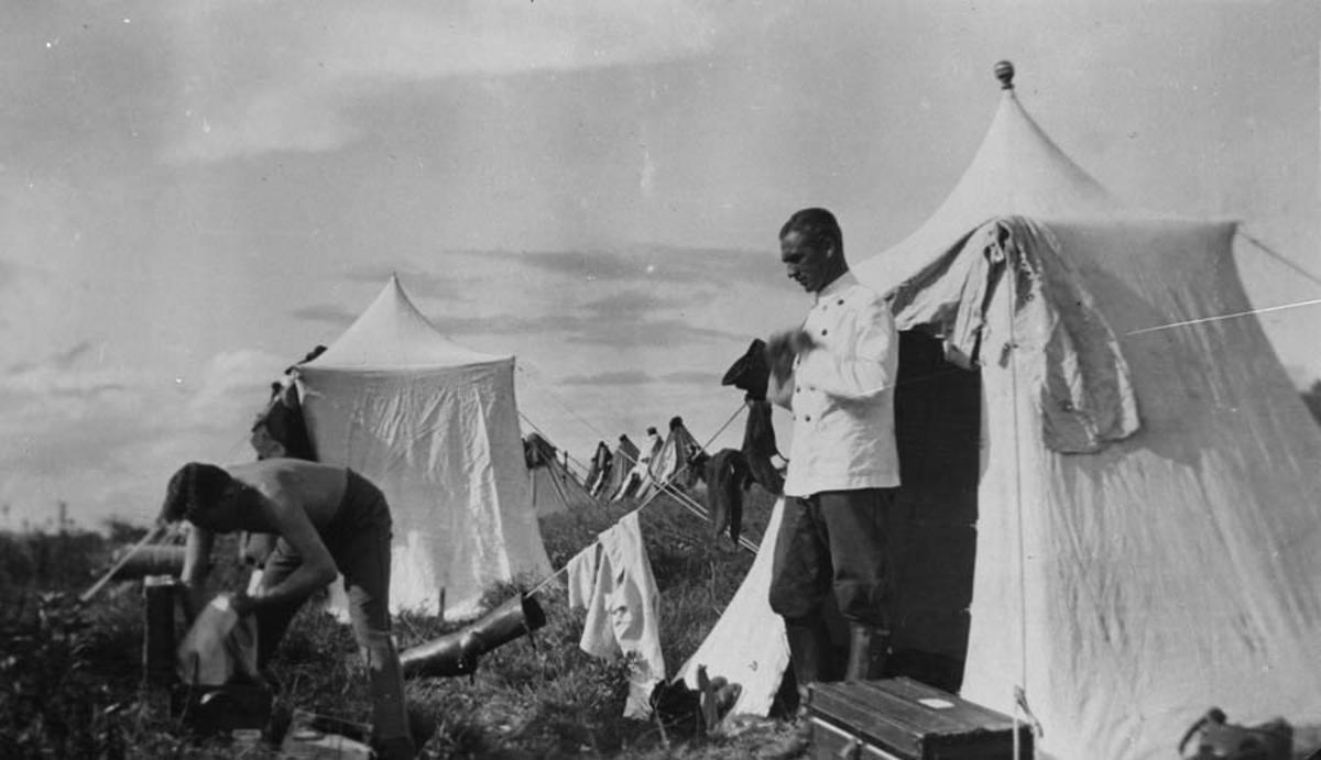 Militær teltleir. Major Hassel i hvit jakke.