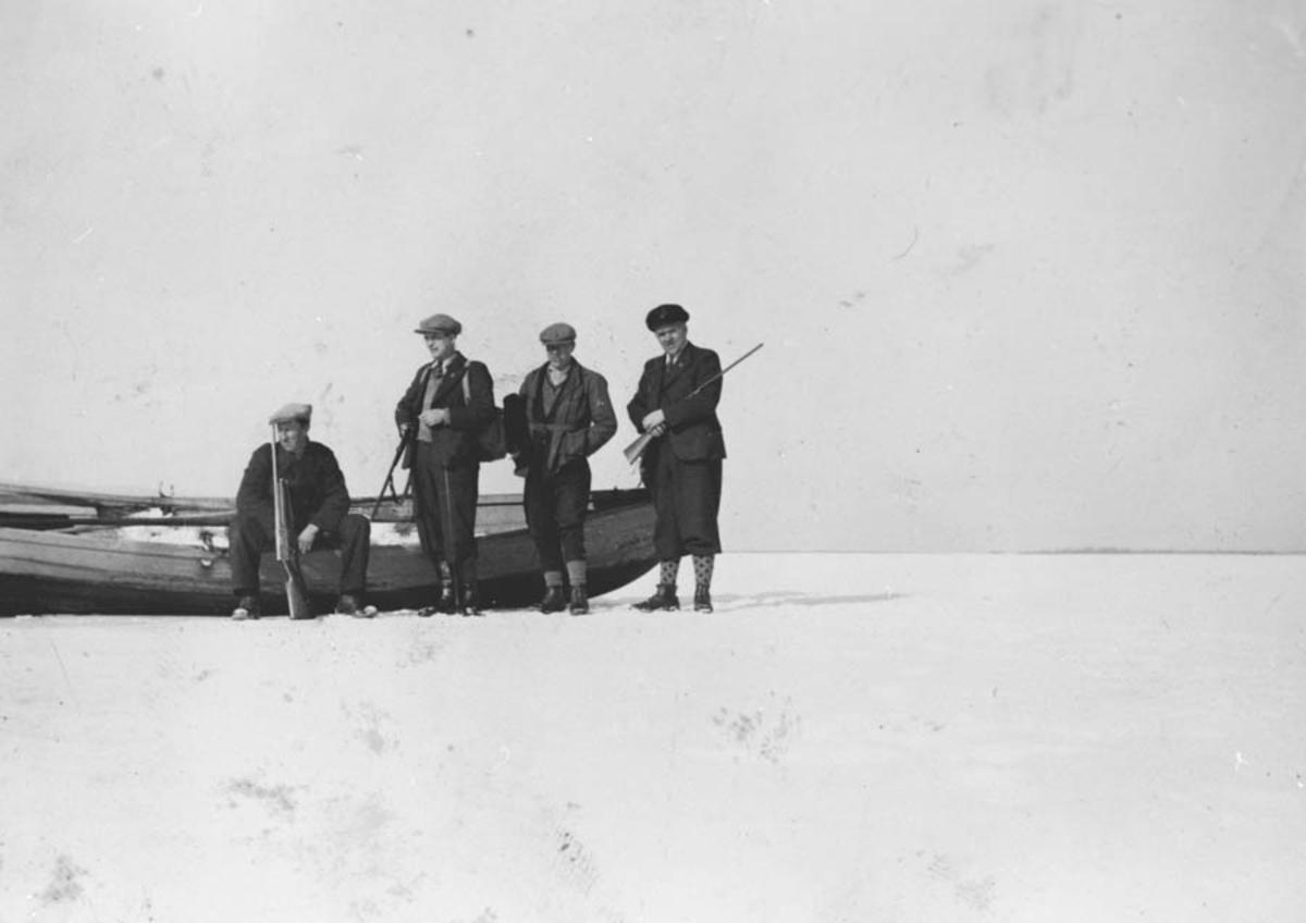 Elgjakt, fire menn ved en båt.