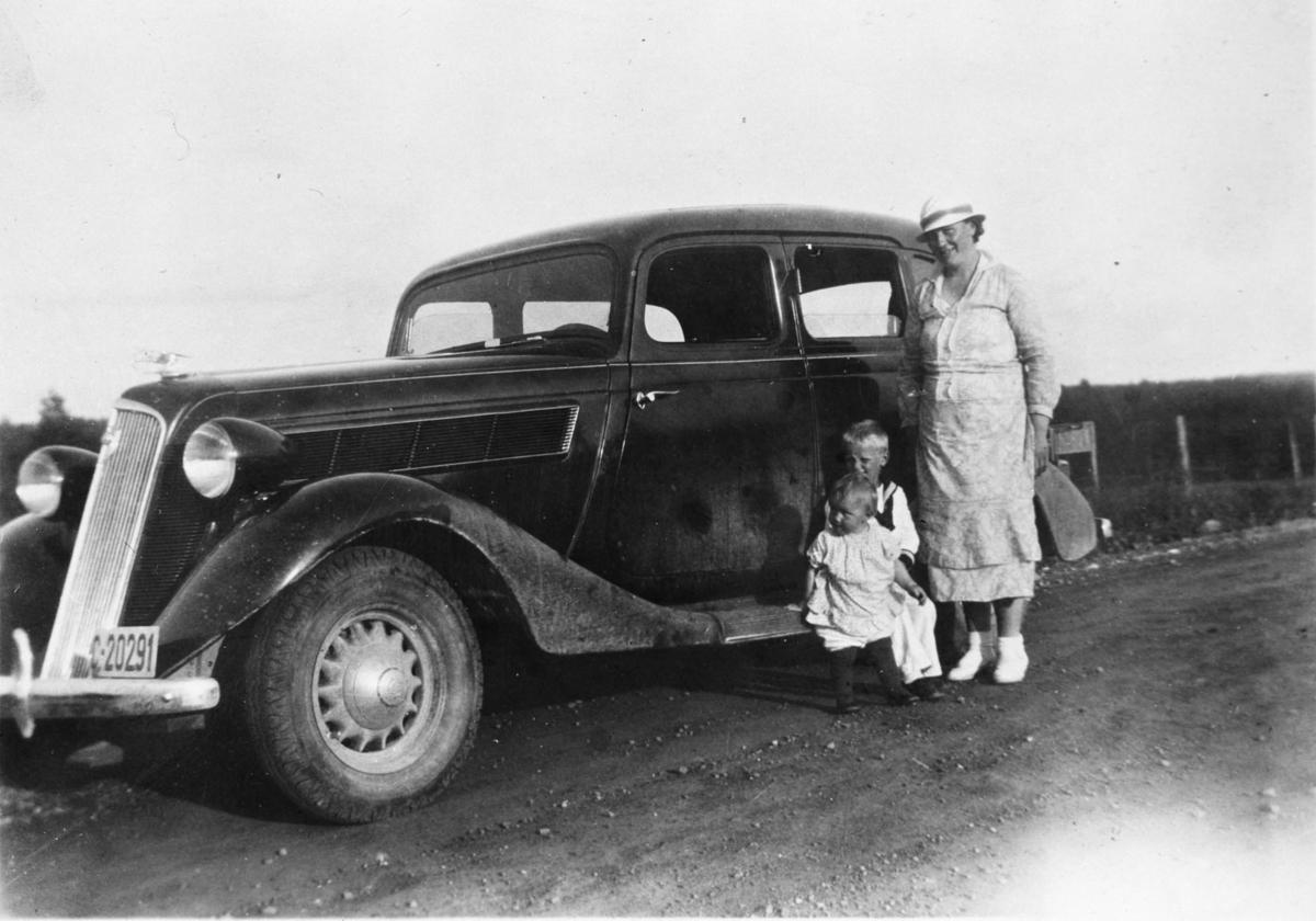 Gyda Feiring og barna står reiseklare foran bilen sin.