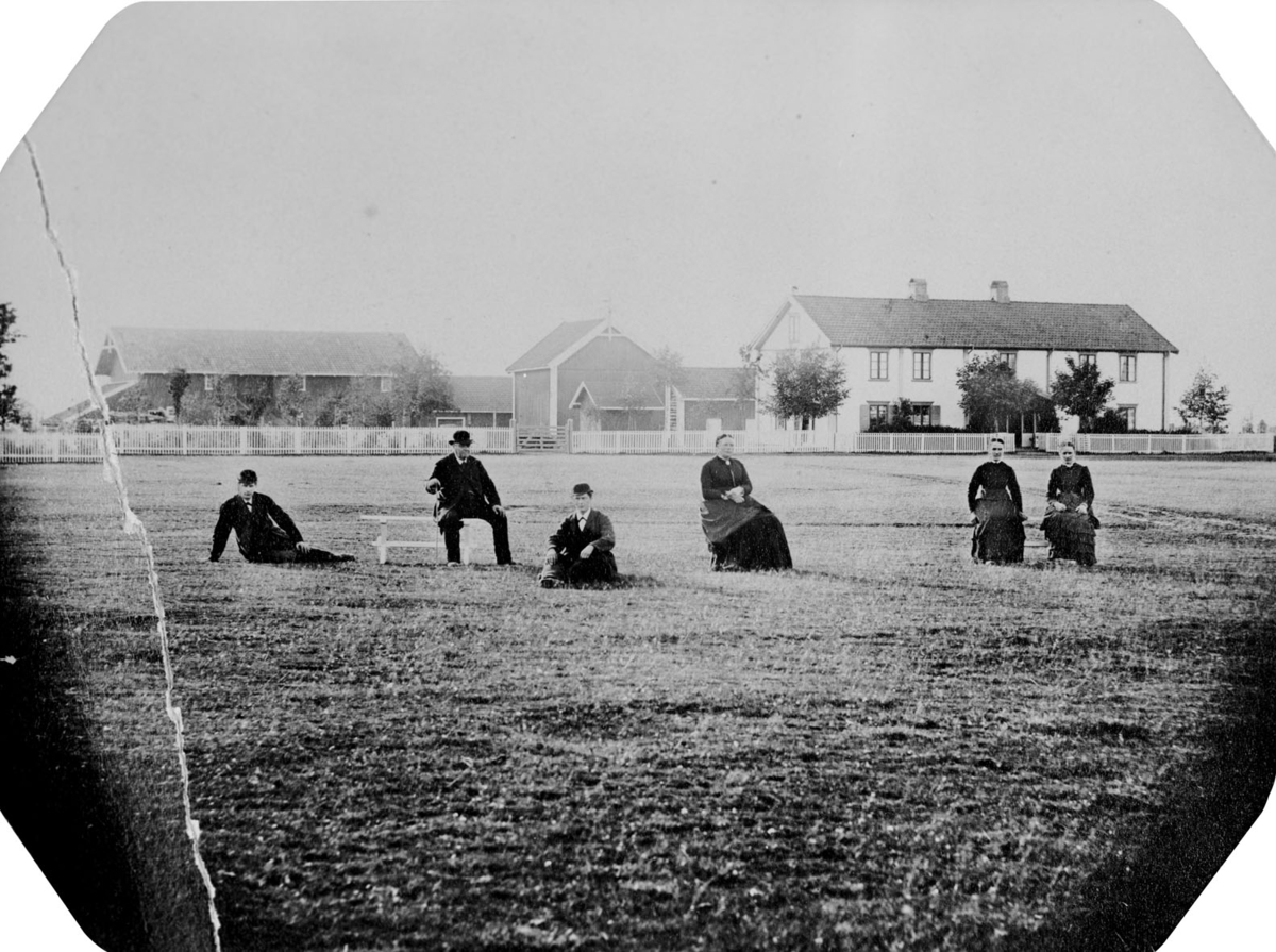 Tre kvinner og tre menn i mørke klær avbildet på en stor plass.