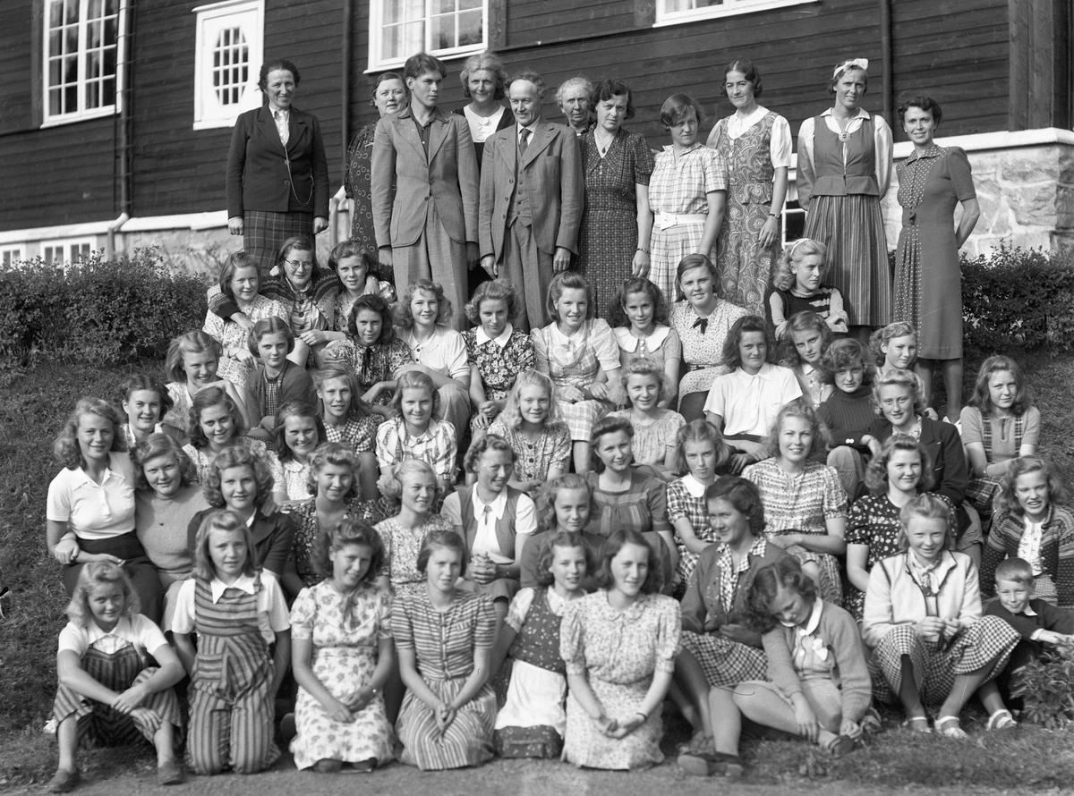 Gruppe voksne og ungdommer utenfor Eidsvoll Landsgymnas. Kan være rektor Jacob Voss med dress og slips bakerst. Han var rektor fra 1922 og fram til 1945.