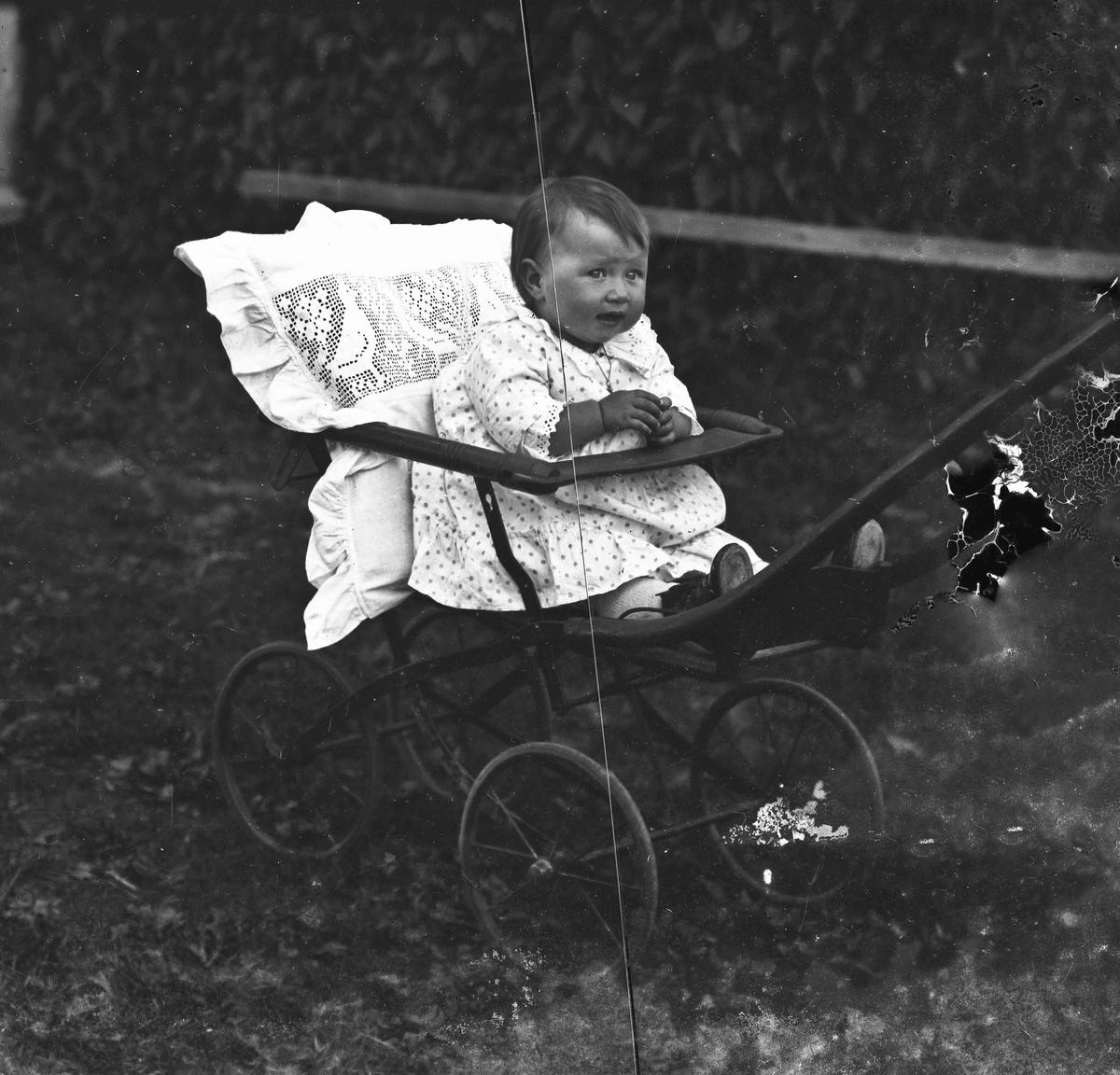 Portrett. Barn sittende i barnevogn