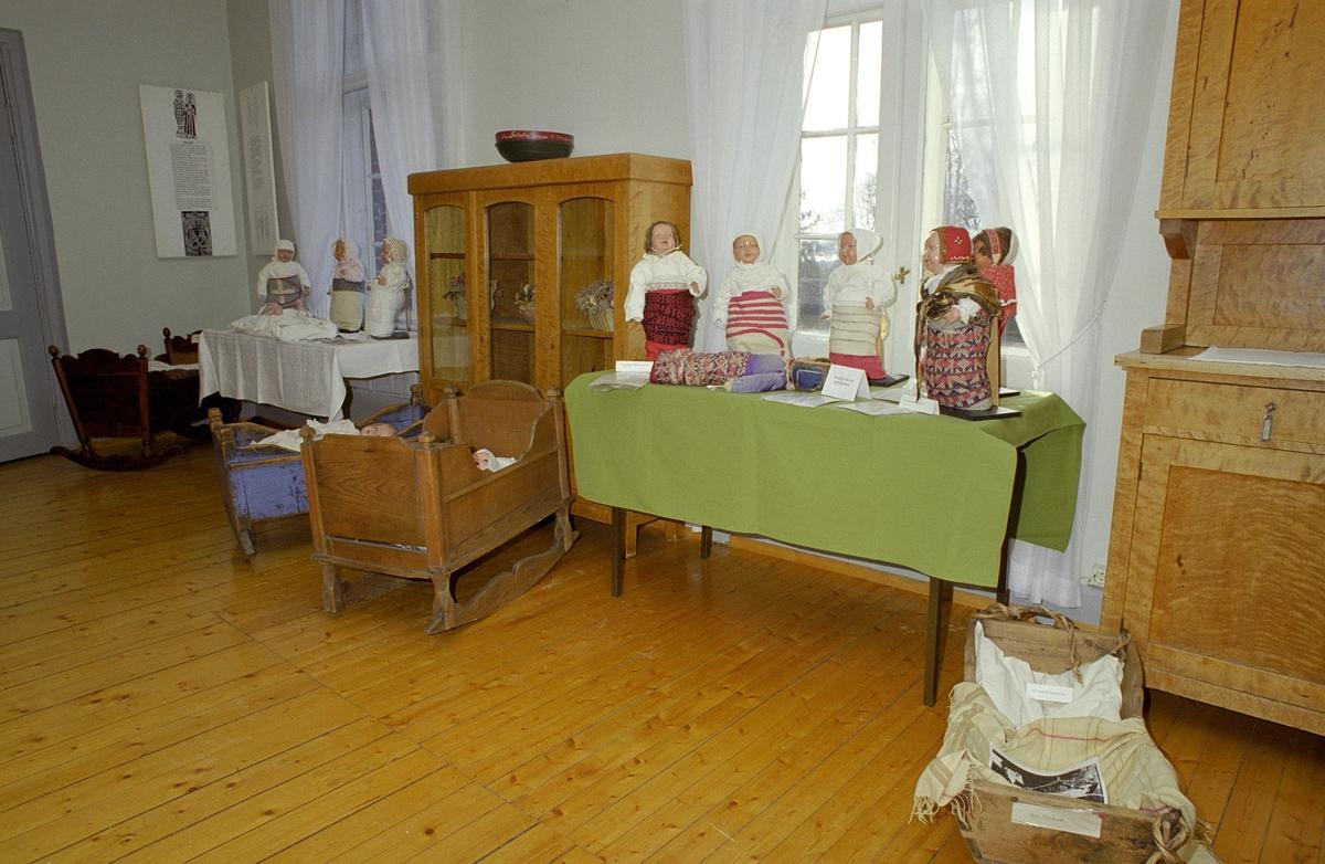 Utstilling. Katti Anker Møller. Bord med dukker, kumser, klær og vugger.