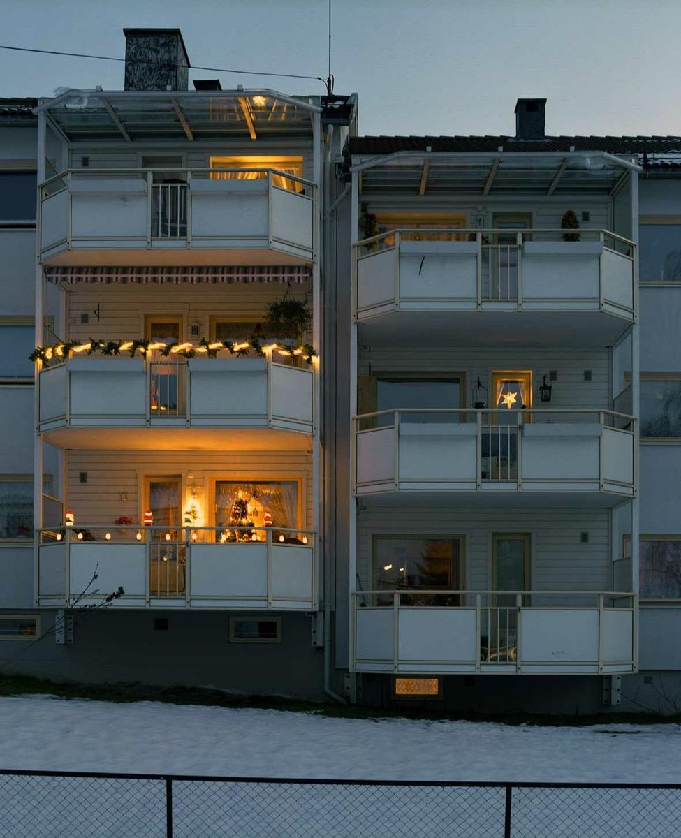 Julebelysning.  Utsmykning på altaner i borettslag. Hvite lysslanger, lysende nisser og stjerne i vindu.