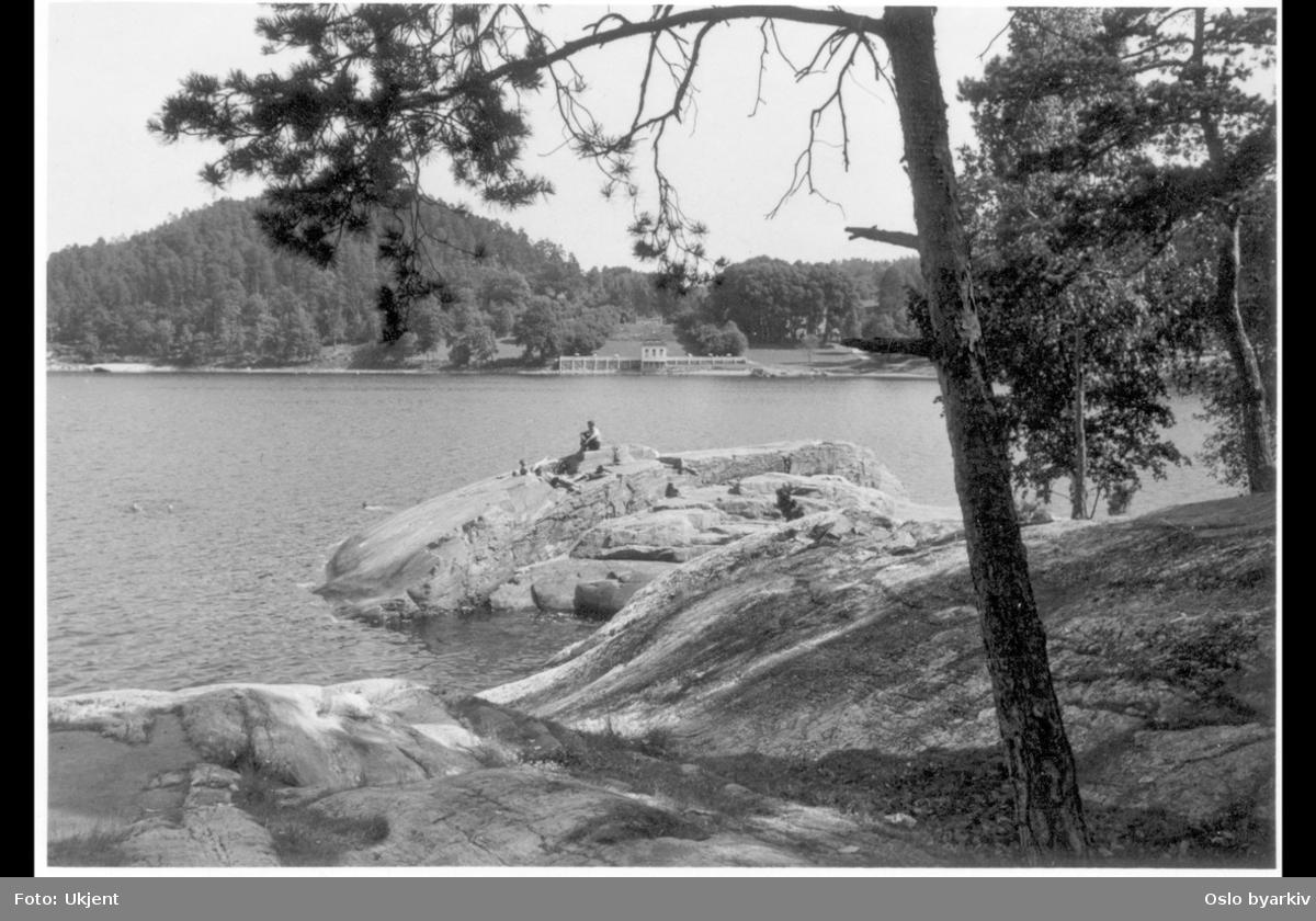 Hvervenbukta sett fra syd mot det tidligere lysthuset (rokokkopaviljongen) til Stubljan gods. Nå kiosk og kafé (uteservering) for badeplassens gjester. (Godsets hovedbygning brant ned i 1913.) Strandknauser.