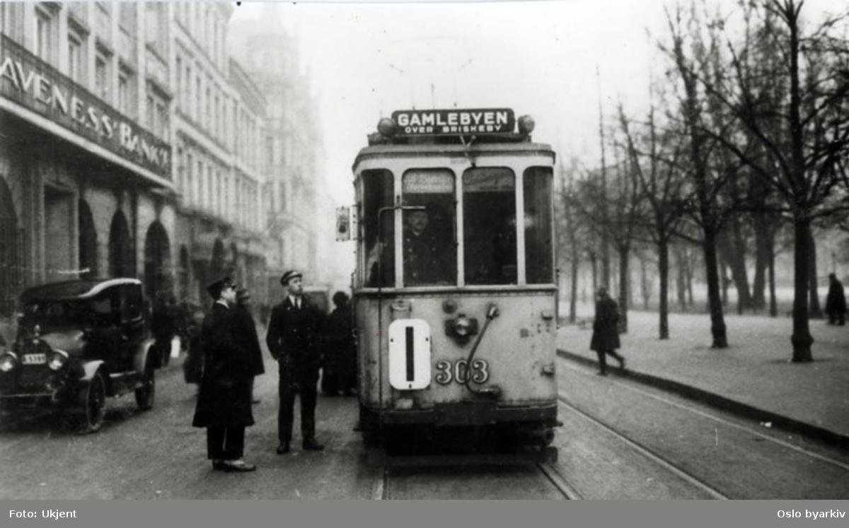Oslo Sporveier. Trikk, motorvogn 303 på linje 1, Majorstuen-Gamlebyen. Her i Stortingsgata ved Klaveness bank. Bildet tatt morgenen 1. januar 1925 da byen skiftet navn til Oslo og bydelen Oslo endret navn til Gamlebyen. Vogna er stoppet av fotografen nettopp av den årsak. T-Ford?