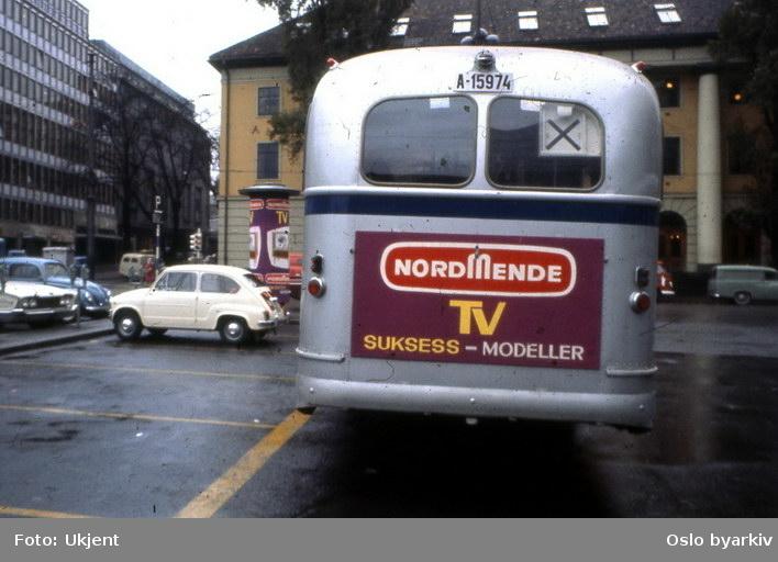 Oslo Sporveier. Sporveisbuss. A-15974 dieselbuss linje X og Fiat 600 på Arbeidersamfunnets plass. Reklame for NordmendeTV. Torggata bad.