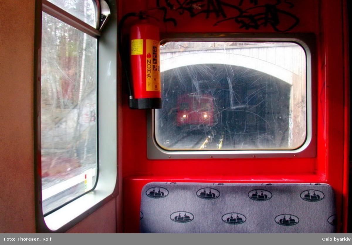 Oslo Sporveier. Østensjøbanen. Innsiden av T-banevogn 1034, serie T1, innkjørsel mot Bogerudtunnelen, møtende tog.