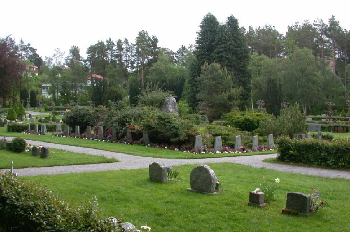 Bautastein (Ca 1,6 m høy) med bronseplate plassert på en liten høyde. beplantning. 23 graver med falne på vest-,nord- og østsiden av bautasteinen. Gravstøttene er likt utformet i 5-6 sm tykk grå skifer. Navnene på gravstøttene står med front utover fra bautasteinen.