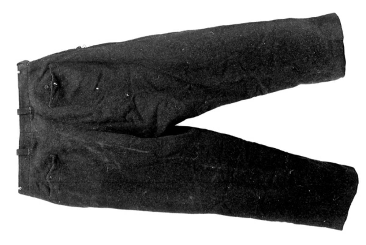 Buksa er av svart vadmel. Den er lappet på begge lårene med svart ullstoff. Linning og lommer av hvitt bomullsstoff. Buksa er brukt under skogsarbeid og tømmerfløting av giveren.