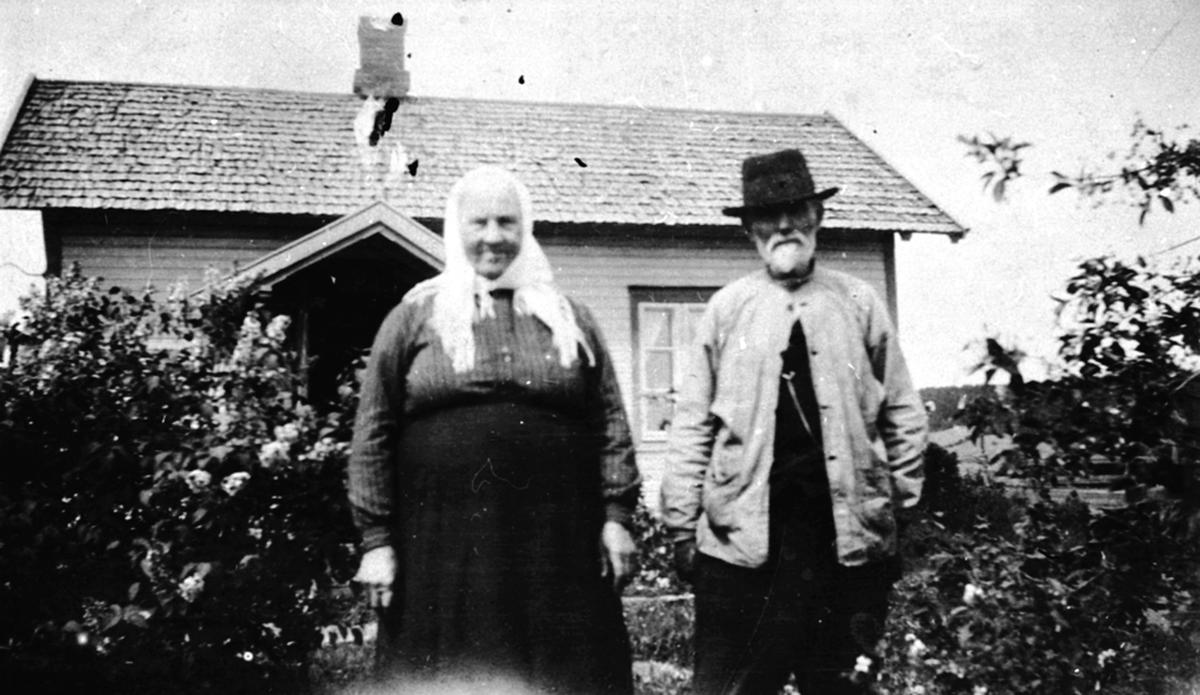 Eldre ektepar foran hus. Karoline Knutsdatter Stensbak f.1848 og Peder Hansen Stensbak f.1850. Stensbak, Nes, Hedmark.