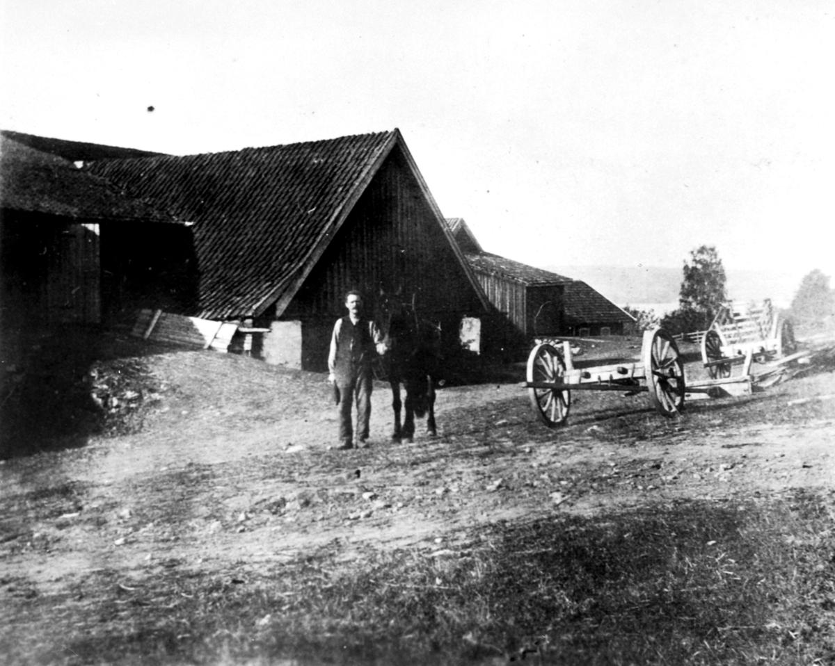 Stallkar Olivius Maurud f.1869 med hest ovenfor gamlelåven på Hovelsrud, Helgøya. Låven brant i 1934.