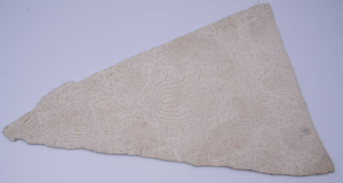 Spissvinklet trekant av hvit lin med matelassé-broderi, regence-ornamentikk symmetrisk motstilt om midtaksen, hjerteformer, stjerner, akantus og to fugler. Bunnen er flere steder oppfylt av små knuter. Baksiden er av grovere lin.
