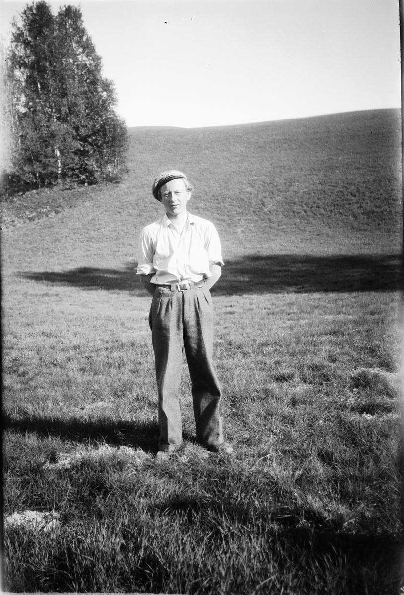 Ukjent mann med cap på en eng.