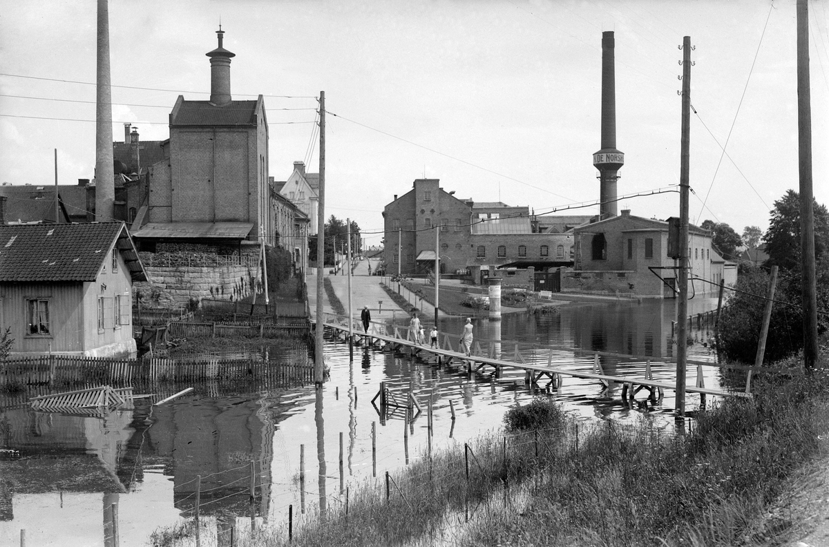 """Bryggeriundergangen i Hamar under flommen i 1927. Huset til venstre tilhørte Melkefabrikken og ble kalt """"Boligen"""". Hamar Bryggeri."""