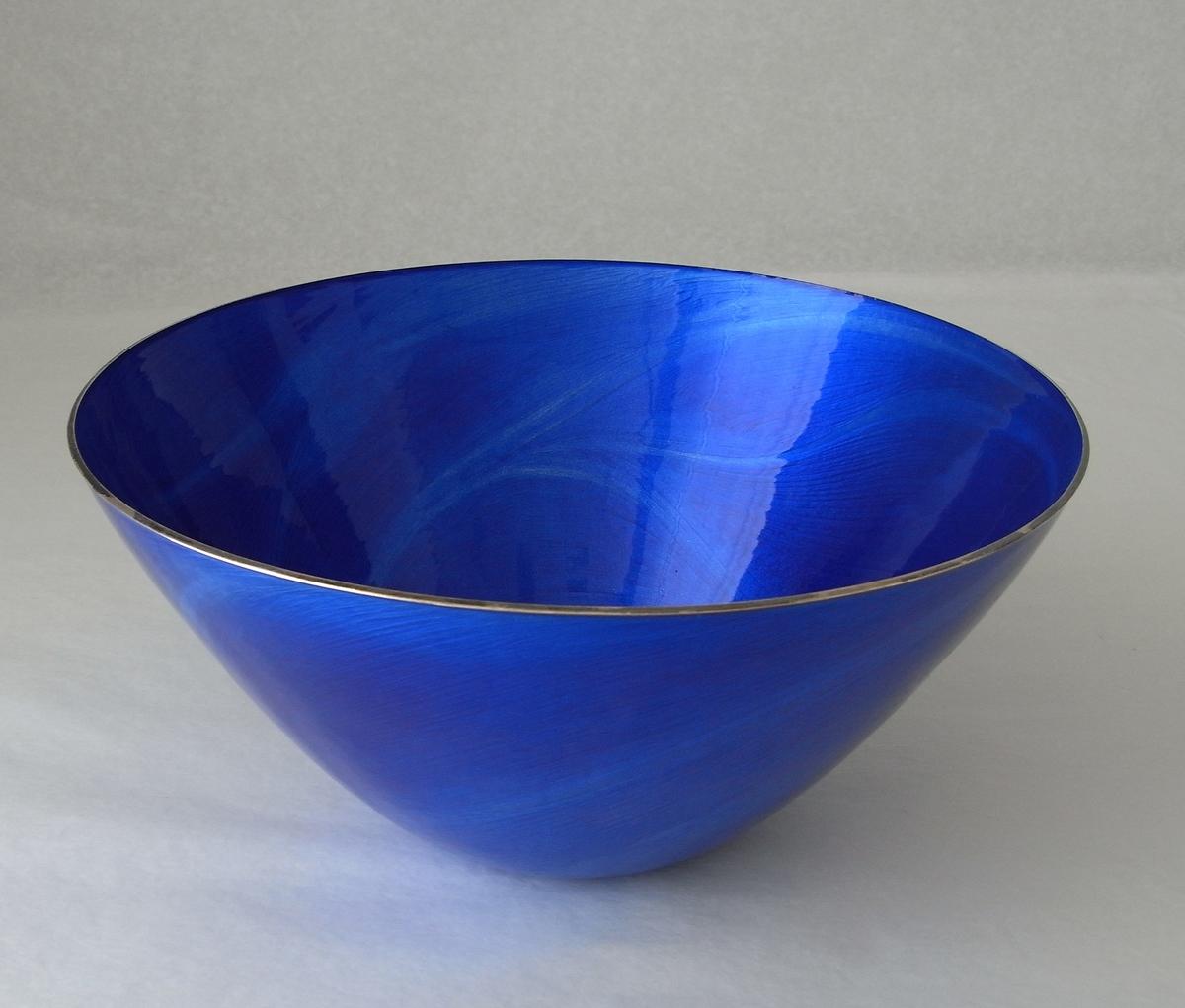 En bolle i sterling sølv med blå speilemalje. Organiske og livfulle fresespor danner et nesten tresnittaktig uttrykk.