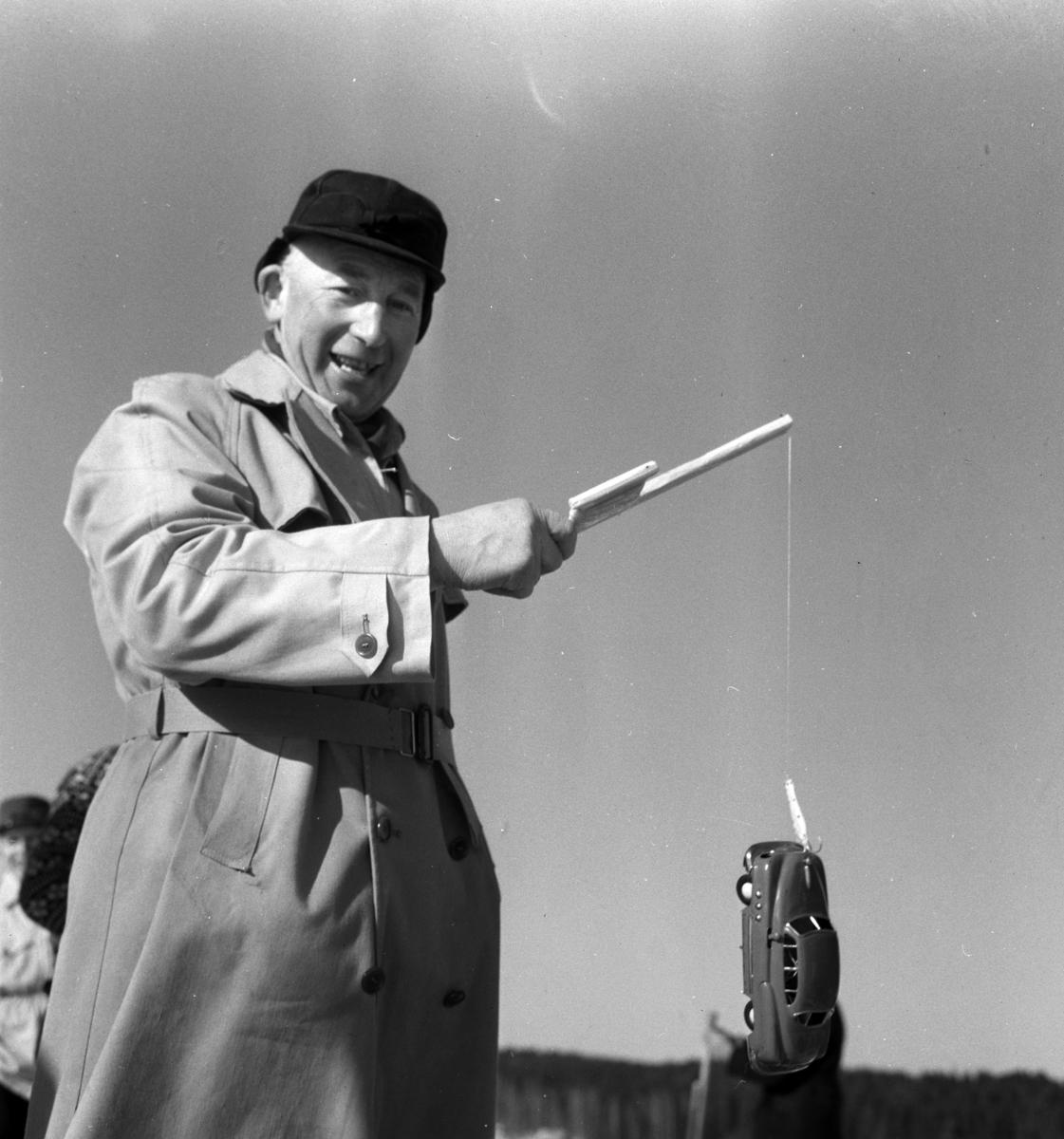 """Nils Bjørnerud, Furnes, vinner av fiskekonkurransen. """"Bilfiske"""" Han vant en Skoda 1958 modell. Pilkekonkurranse utenfor Strandsaga i Brumunddal 09. 03. 1958. Pilkekonkurranse utenfor Strandsaga i Brumunddal 09. 03. 1958. Fiskekonkurranse på Mjøsisen. Isfiske.  Premier i pilkekonkurransen var bla. en bil, Skoda 1958 modell, motorsykkel, kjøleskap, reiseradio. Se. Na-00293-31 og Na-00293-32 for flere opplysninger."""
