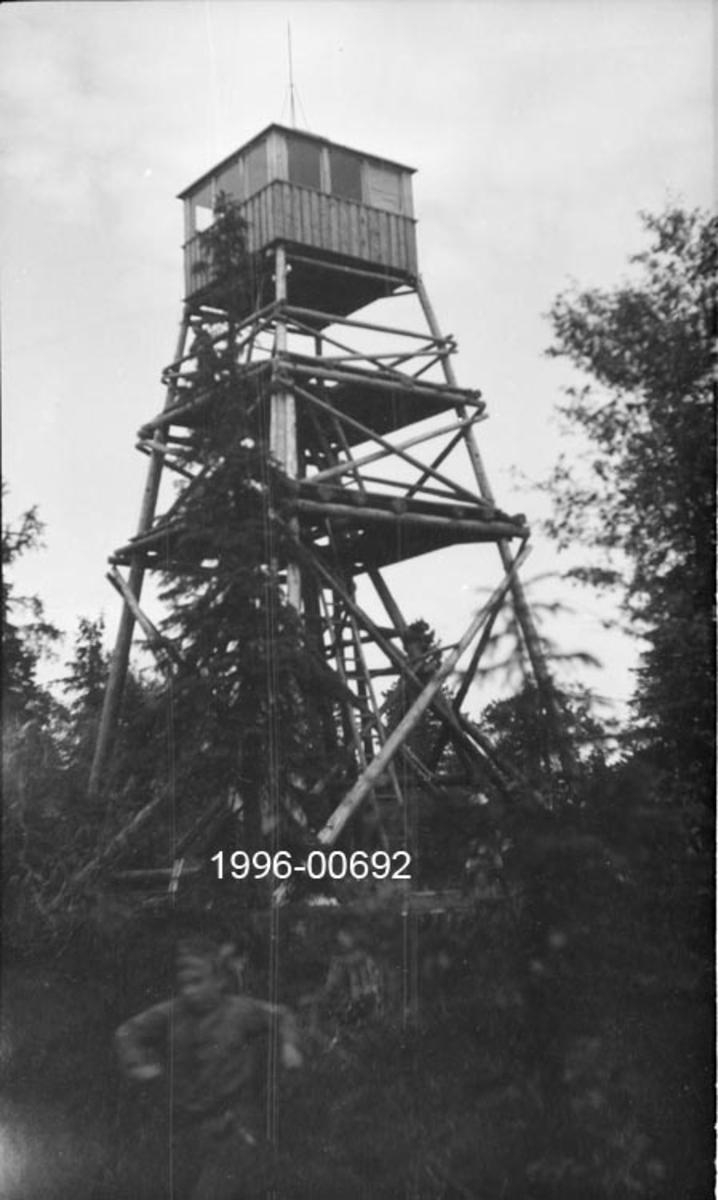 Tårnet på Skjennungsåsen skogbrannvaktstasjon i Nordmarka utenfor Oslo.  Brannvaktstasjonen her skal ha vært etablert i samarbeid mellom skogeierne Løvenskiold og Oslo kommune i 1930.  Tårnet på fotografiet ble bygd i 1932 med støtte fra forsikringsselskapet Skogbrand.   Tårnet er en åpen stolpekonstruksjon.  Det har noenlunde kvadratisk grunnplan.  Hjørnestolpene skrår bratt mot hverandre og er avstivet med krysslagte stokker i tre nivåer på alle fire sider.  Mellom hvert nivå er det innlagt plattinger med golv og stigeforbindelse videre oppover mot luka i golvet på utkikkshytta.  Hytta er utført i bordkledd bindingsverk og har sammenhengde vindusrekker i alle himmelretninger under pyramidetaket.  På toppen av taket er det montert en lynavleder.  Tårnet står på et berg omgitt av spredt barskog.
