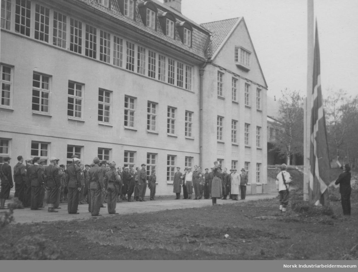 Flagget heises ved fabrikkens kontorbygning mai 1945.
