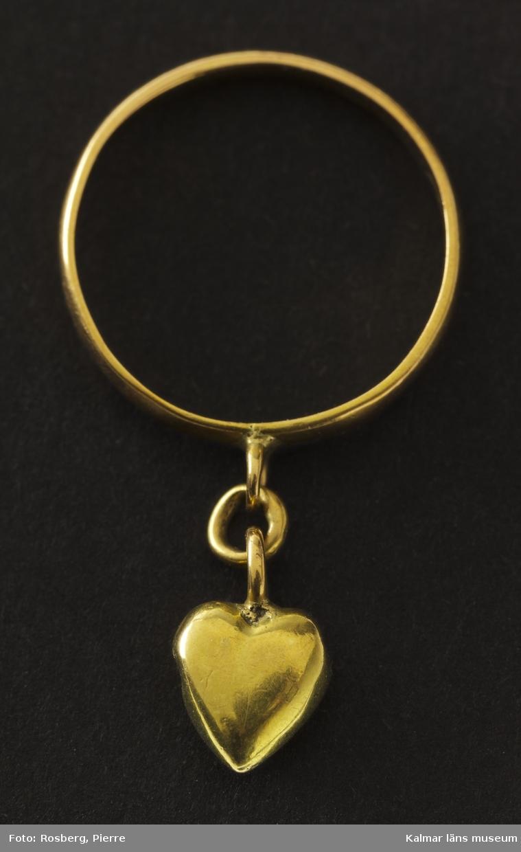 KLM 28690:77 Ring, av guld. Fingerring? Inre diam 1,4 cm, ringskenans bredd 0,17 cm. En mycket liten guldring, skenan slät och jämnbred och försedd med en ögla, från vilken det hänger ett litet guldhjärta. Gravering på insidan: Minne. Utan stämplar.