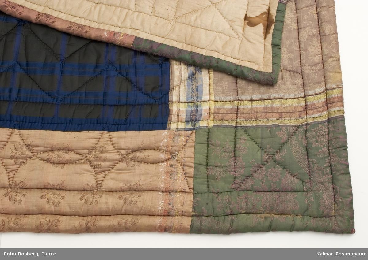 KLM 39365:1 Täcke av siden och bomullstyg. Bröllopstäcke. Täcke sytt av olika mönstrade och färgade sidentyger. Bred bård av ljusa tyger. Hörnen på täcket, är av grönt sidentyg. Spegel av svart och blårutigt siden. Täcket är stickat med foder av beigt bomullstyg. Stoppning av vadd. Tillverkat före 1920.