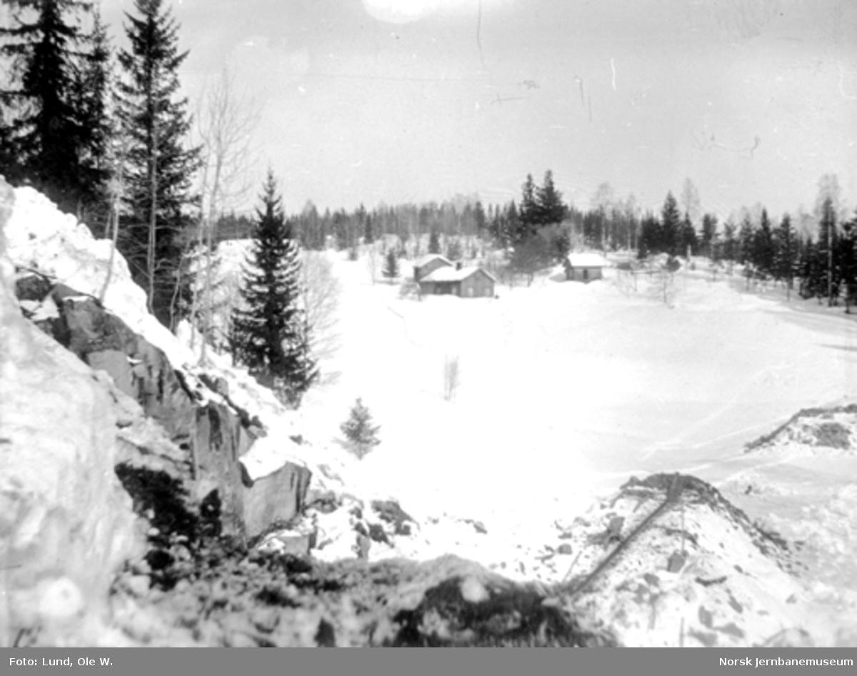 Fra anlegget av Holmestrand-Vittingfossbanen : vinterbilde med en fylling fra Leikåsskjæringa mellom Haslestad og Kleppan og med et gårdsbruk i bakgrunnen