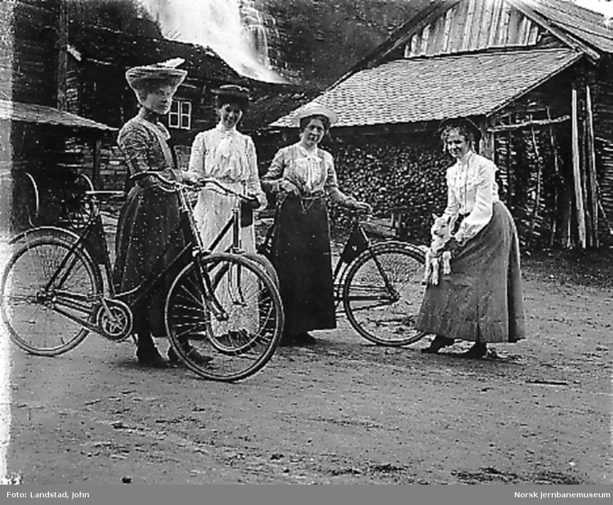 Tre damer med sykkel på et gårdsbruk, trolig navn Framnes