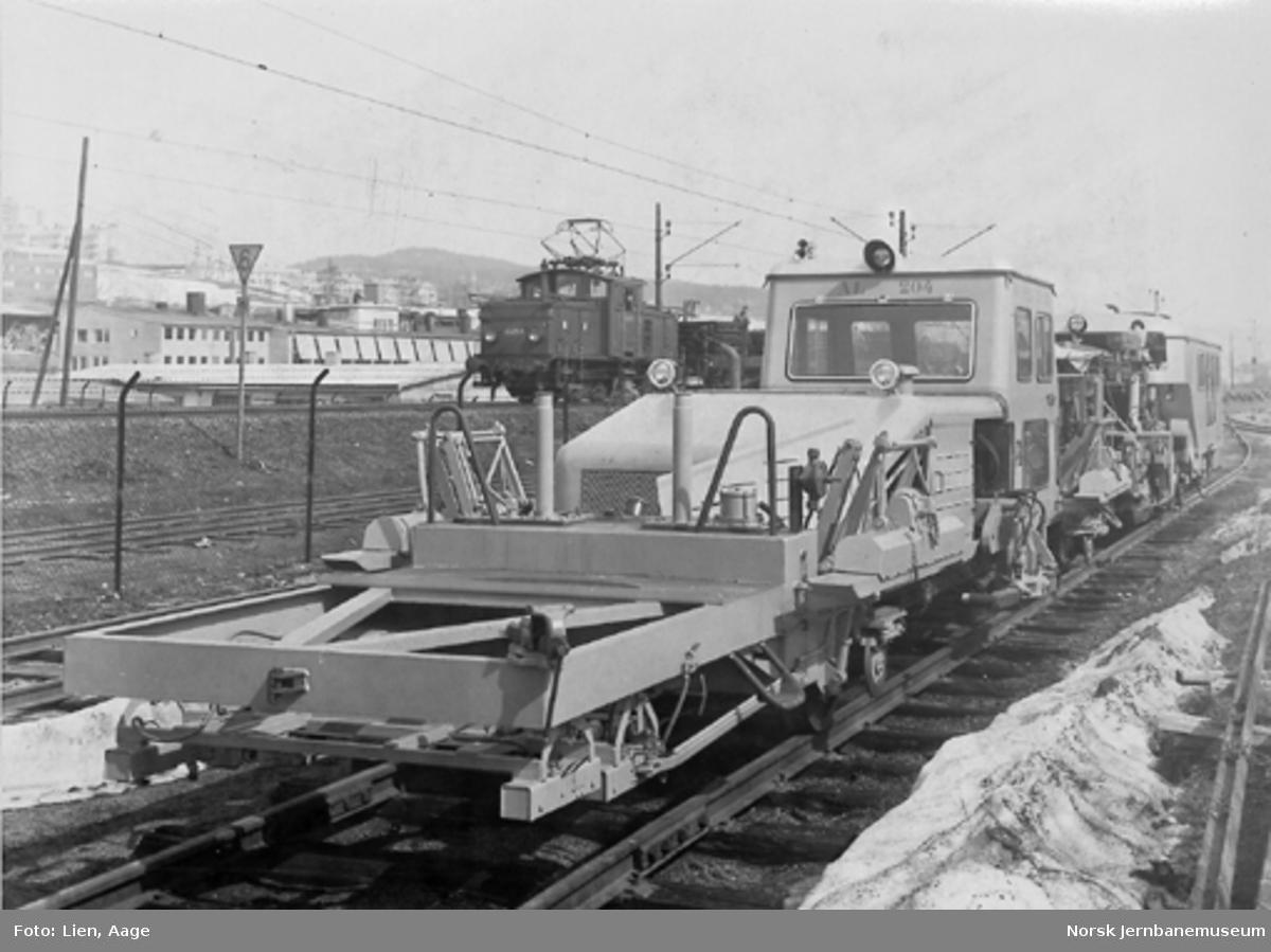 Sporbaksemaskin fra Plasser & Theurer type AL204, NSB nr. 91-05 : elektrisk skiftelokomotiv El 10 2513 i bakgrunnen
