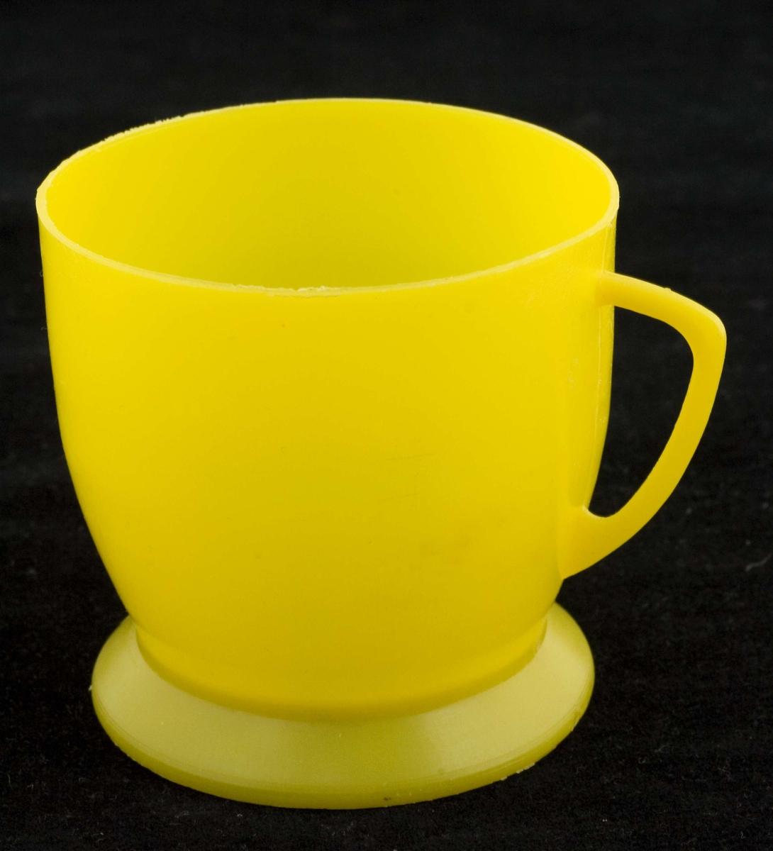 Målebeger med hank i gul plast. Desiliterangivelse på innsiden. Navn på vaskemiddelprodusent står på undersiden.