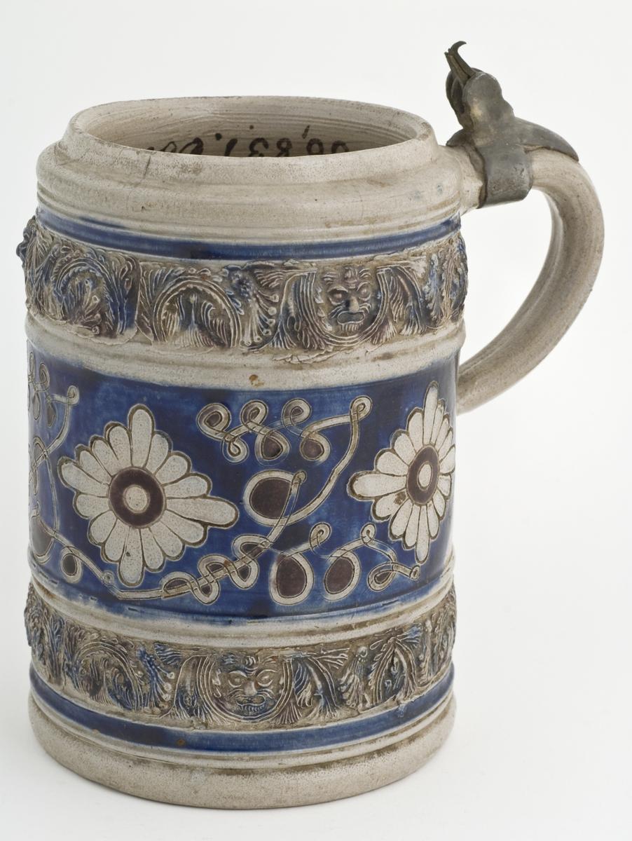 """Krus i grå keramikk av en type som stammer Westerwald-området i Tyskland. Karakteristisk er risset og stemplet dekor og pålagte relieffer, farget med koboltblå og senere også manganfiolett, under klar saltglasur. Dette lave sylinderformede kruset kalles """"Humpen"""" og ble masseprodusert gjennom hele 1600 og 1700 tallet.   Lokk manbler men hengsel på hank er igen. Risset dekor i form av blomster."""