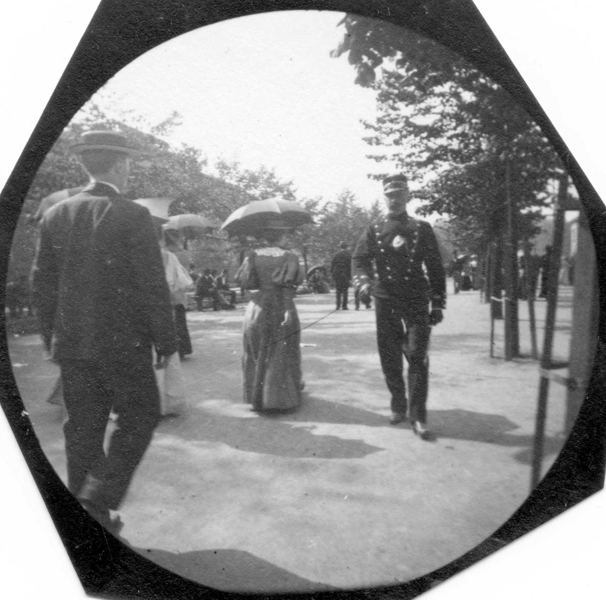 Mennesker spaserer langs Karl Johans gate, Oslo.  Mann med dress med ryggen til, damer med parasoller og rittmester Michelet i uniform kommer mot fotografen.