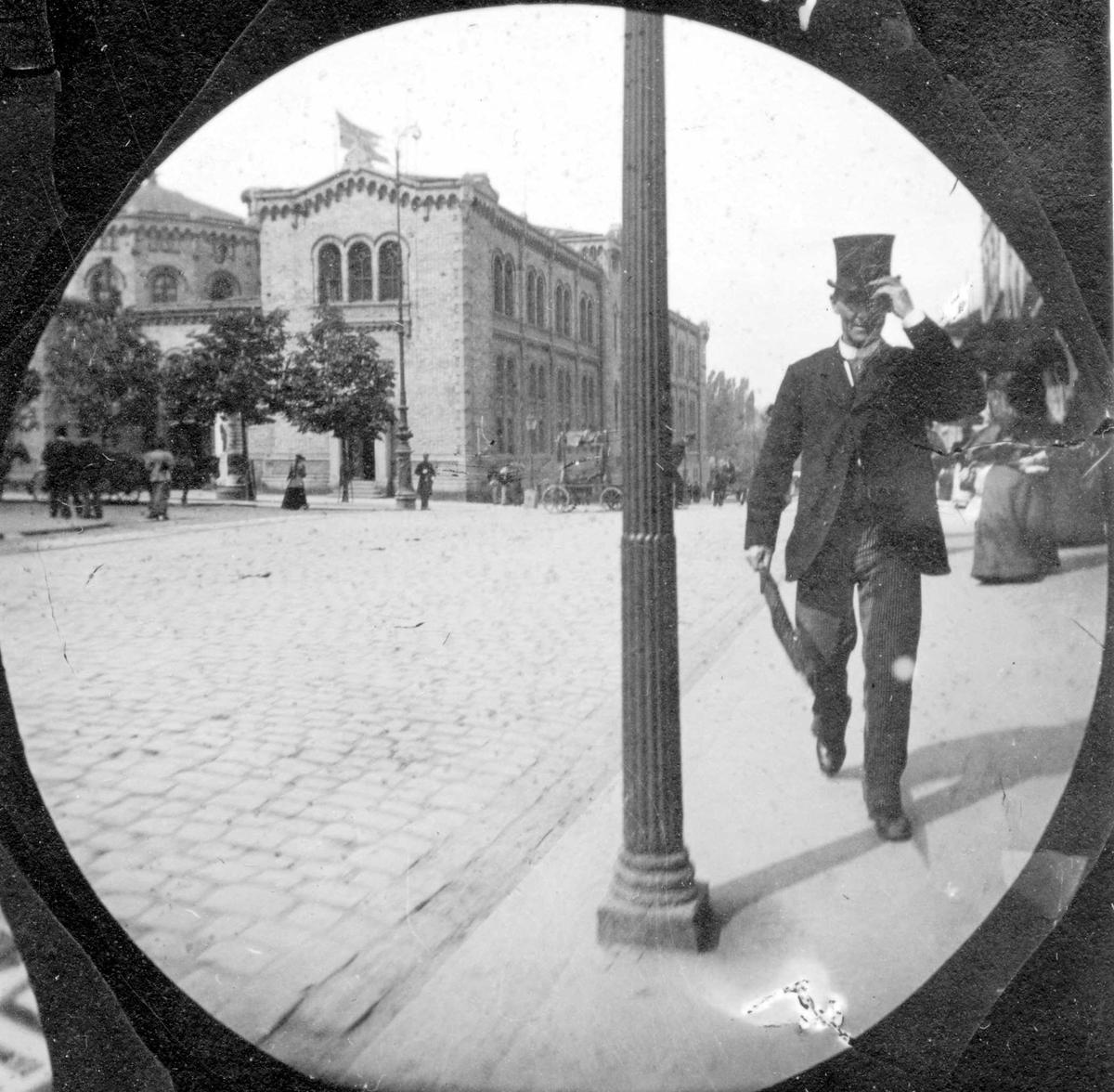Professor Geelmuyden spaserer langs Karl Johans gate, Oslo, mot Egertorvet med Stortinget i ryggen.