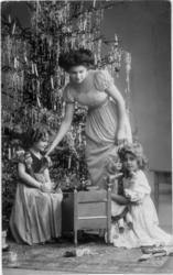 Postkort, stemplet 1909. Kvinne og barn foran juletre.