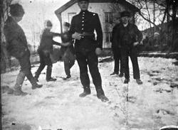 Gruppe menn og gutter morer seg på gårdstunet, Lunden gård,