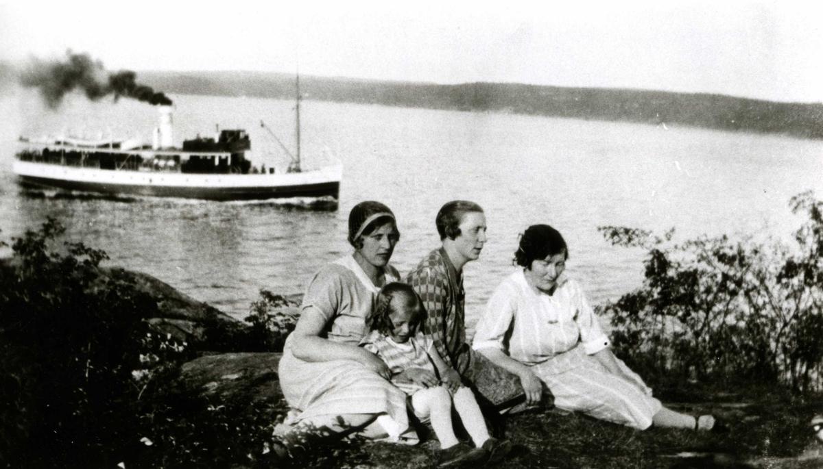 To kvinner, en mann og et barn sitter på bakken med ryggen mot sjøen. I bakgrunnen Nesoddbåten på vei innover Bunnefjordsen. Ferieliv på Oslo Godtemplarungdomslags feriehjem Kirkevik, Nesodden