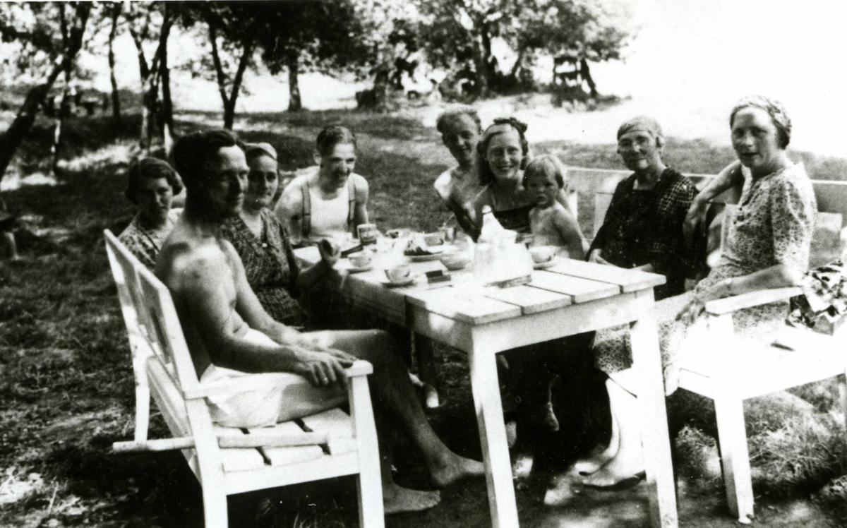 Måltid i det fri. Gruppe voksne og barn på Oslo Godtemplarungdomslags feriehjem Kirkevik, Nesodden, ca 1940