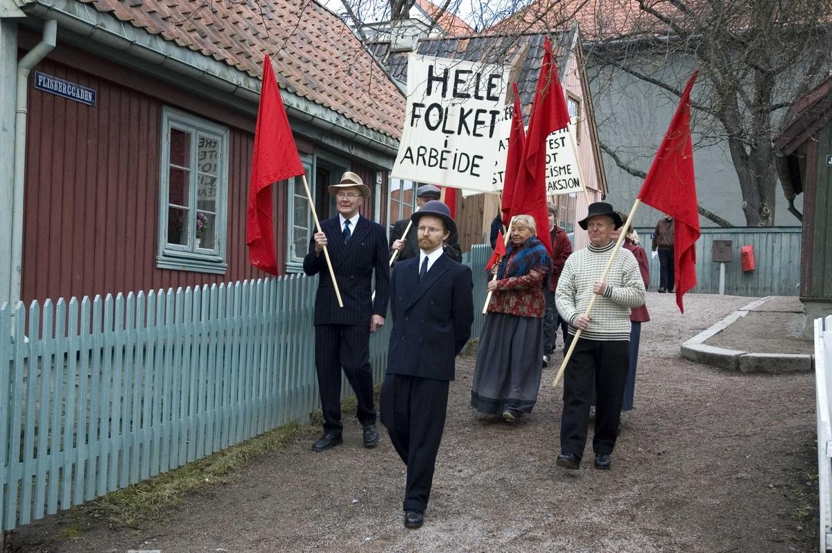 1.mai 2006 på Norsk Folkemuseum. Demonstranter med plakater og røde faner i museets gamleby, her på Enerhaugen.