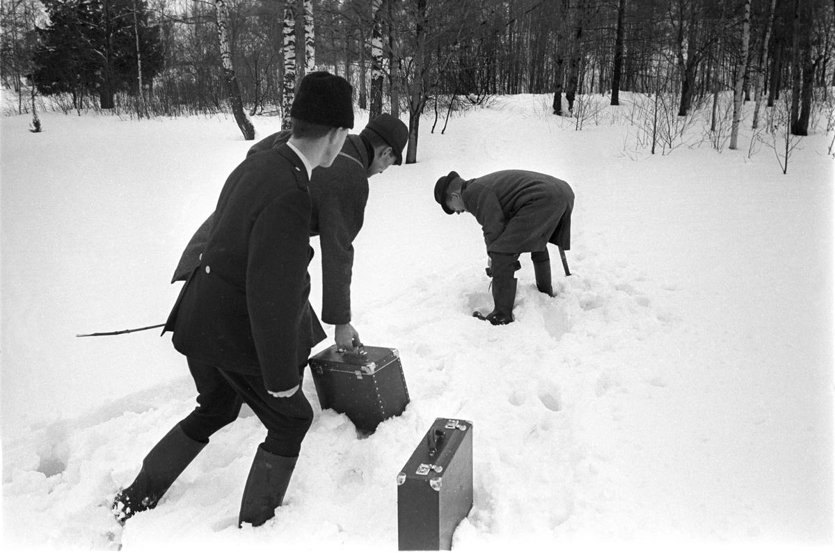 Politietterforskere på åstedsbefaring. Politiet ettersøker en voldsforbryter i skogsområdet rundt Brannfjell i februar 1961. Her tas det prøver i snøen.