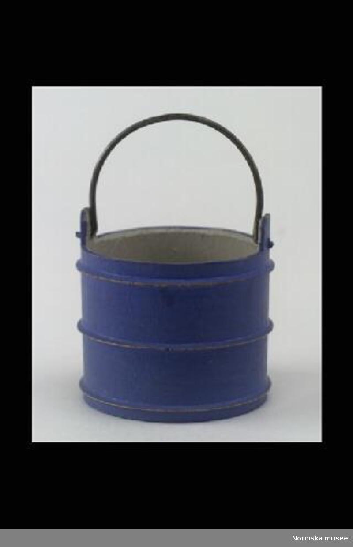 Inventering Sesam 1996-1999: H 5,3 cm Diam 5,4 cm Vattenså (hink) svarvad i trä.Rund med raka sidor. Utvändigt blåmålad och med tre horisontella åsar (imiterande tunnband). Invändigt gråmålad. Ledad tvärgrepe av metalltråd. Tillhör dockskåp inv.nr 213.734, rum VIII, kök. Dockskåpet tillverkat av givaren omkring 1900-1905 i Skinnskatteberg. Leif Wallin jan 1998