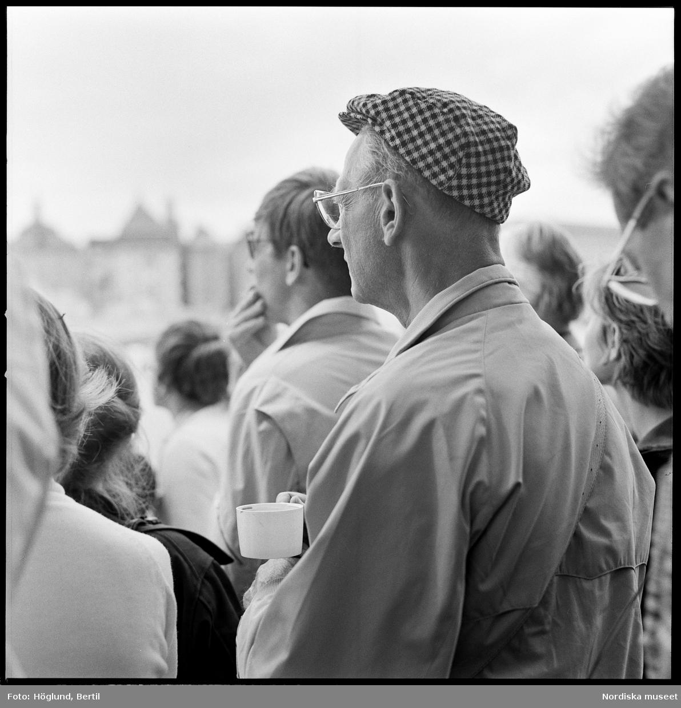Kungabröllopet den 19 juni 1976, Carl XVI Gustaf gifter sig med Silvia Sommerlath. Dokumentation av människor längs kortegevägen. Åskådare, man med keps.