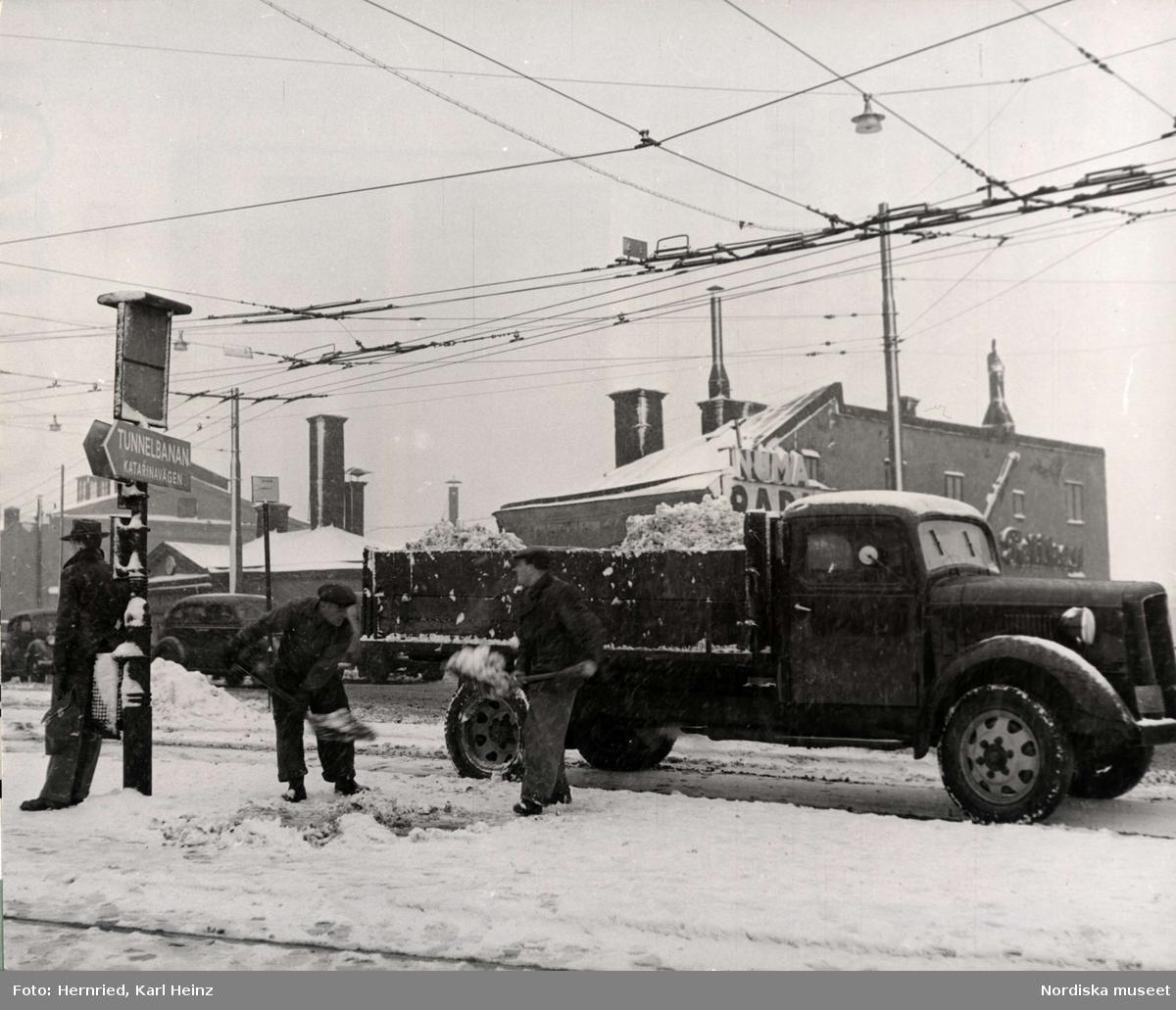 Gaturenhållning. Snöröjningsarbete med skovlar och lastbil på Södermalm i Stockholm