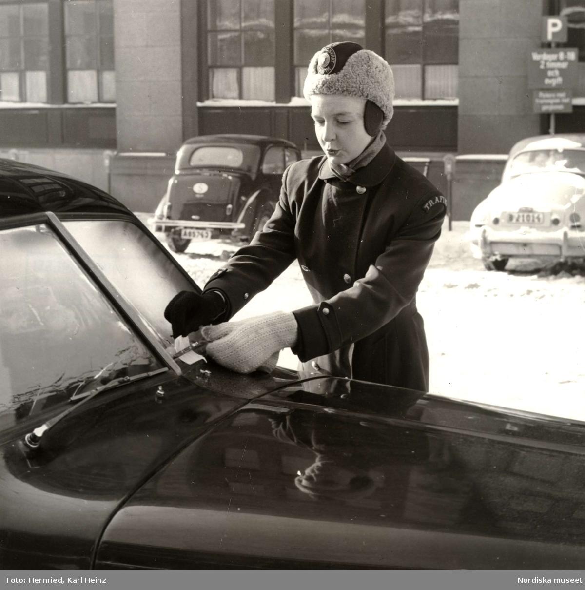 Parkeringsvakt i vinterkläder fäster böteslapp på felparkerad bil.