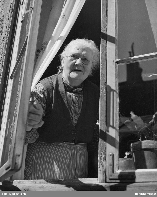 Göteborg. En äldre kvinna som tittar ut genom ett öppet fönster