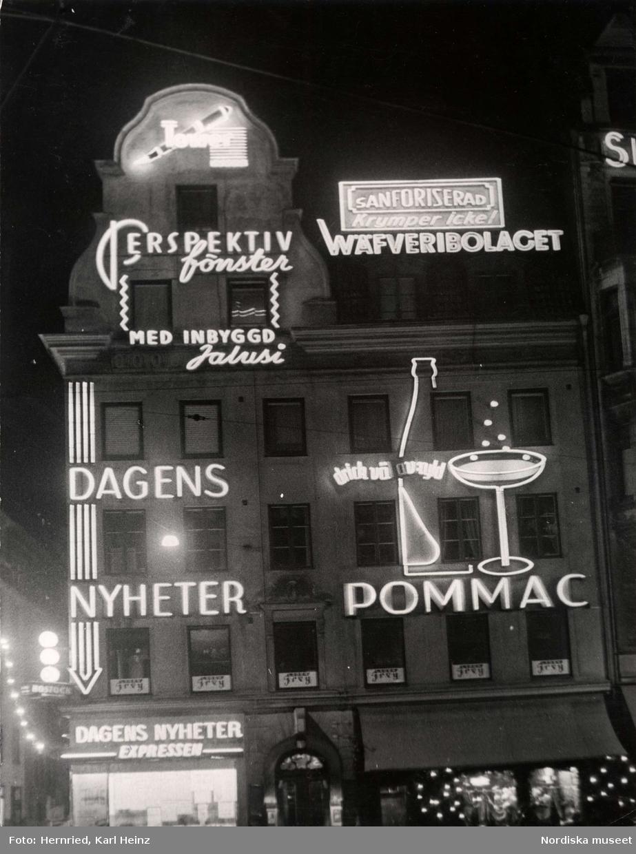 """Reklamskyltar i neon på husfasad för """"Wäfveribolaget – Sanforiserad –krymper icke!"""", Dagens Nyheter, Expressen, """"Pommac – drick väl kyld"""", Tower och Perspektivfönster""""."""