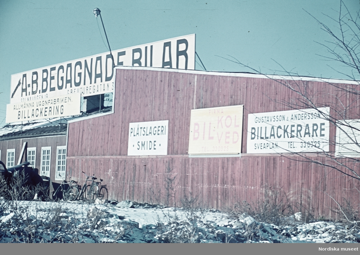 """Plank med reklamskyltar. """"A.B. Begagnade bilar"""""""