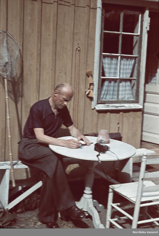En man troligen fotograf Gunnar Lunhdh sitter vid ett trädgårdsbord. En kamera står på bordet.