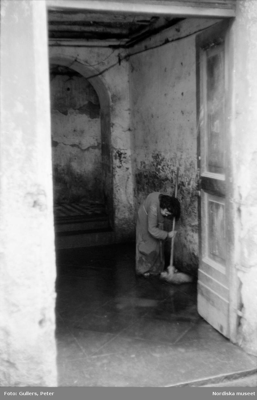 Äldre kvinna svabbar golv i entré. Italien