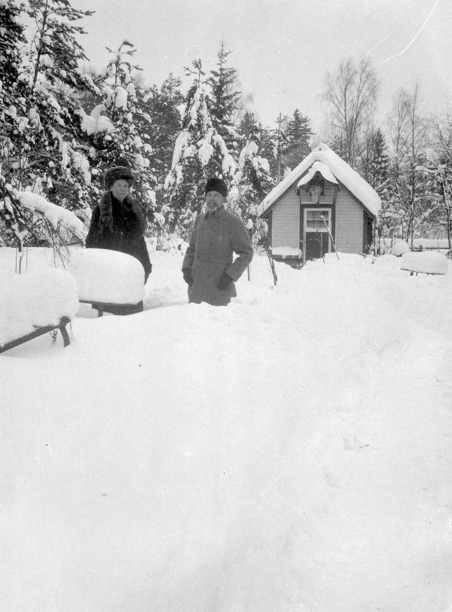 Vinterbild. En man och en kvinnan utanför stuga.