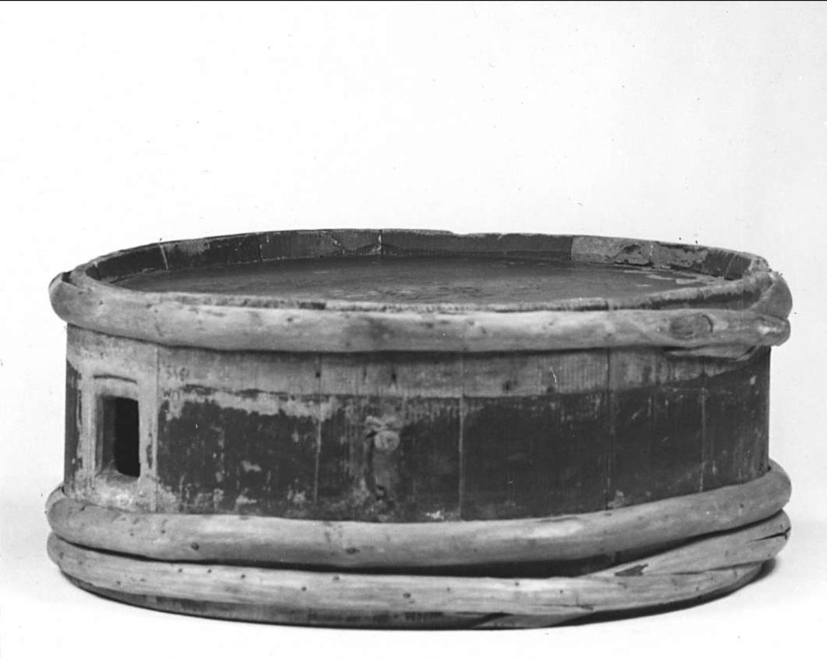 Flaska av trä, rödmålad, utom banden. Järnöglor på sidorna med rester av rep. På ena sidan inristat: 2 KAN 4 KVART DES 1851.